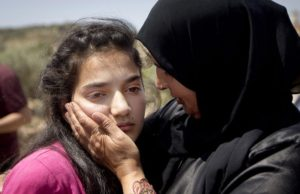 Sabha al-Wawi, right, Palestinian mother of 12-year-old Dima al-Wawi, imprisoned by Israel for allegedly attempting to carry out a stabbing attack, comforts her daughter, after her release from an Israeli prison, at Jabara checkpoint near the West Bank town of Tulkarem, Sunday, April 24, 2016. Al-Wawi who was imprisoned after she confessed to planning a stabbing attack in a West Bank settlement has been released Sunday. (AP Photo/Majdi Mohammed))
