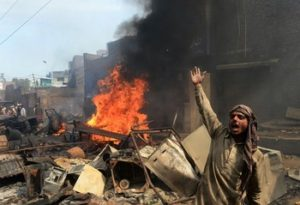 An angry Pakistani Muslim demonstrator shouts slogan beside burning Christian's belongings during a protest over a blasphemy row in a Christian neighborhood in Badami Bagh area of Lahore on March 9, 2013. Thousands of angry protestors on March 9 set ablaze more than 100 houses of Pakistani Christians over a blasphemy row in the eastern city of Lahore, officials said. Over 3,000 Muslim protestors turned violent over derogatory remarks allegedly made by a young Christian, Sawan Masih, 28 against Prophet Muhammad in a Christian neighboorhood in Badami Bagh area. AFP PHOTO/ ARIF ALI (Photo credit should read Arif Ali/AFP/Getty Images)