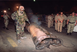 A US soldier (r) and Saudi police officers (l) examine the wreck of a missile, believed to be a Soviet-made Scud, which landed downtown Riyadh 22 January 1991 when Iraq launched a missile attack o the Saudi capital. (Photo credit should read PASCAL GUYOT/AFP/Getty Images)