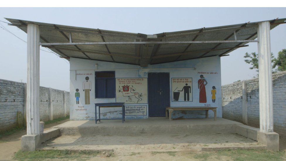 Exterior of toilet facility with images of men and women written on walls