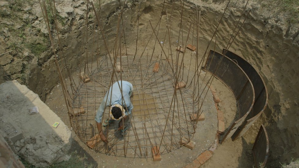 A man in a large hole constructing a biodigester with iron wires