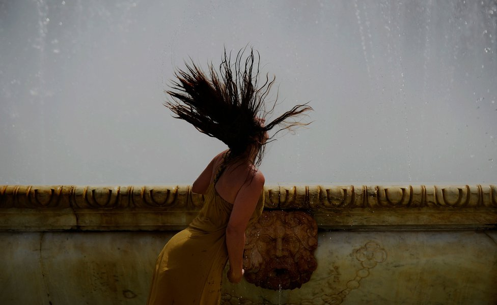 A woman refreshes herself in a fountain at Plaza de Espana, on a hot summer day in Sevilla