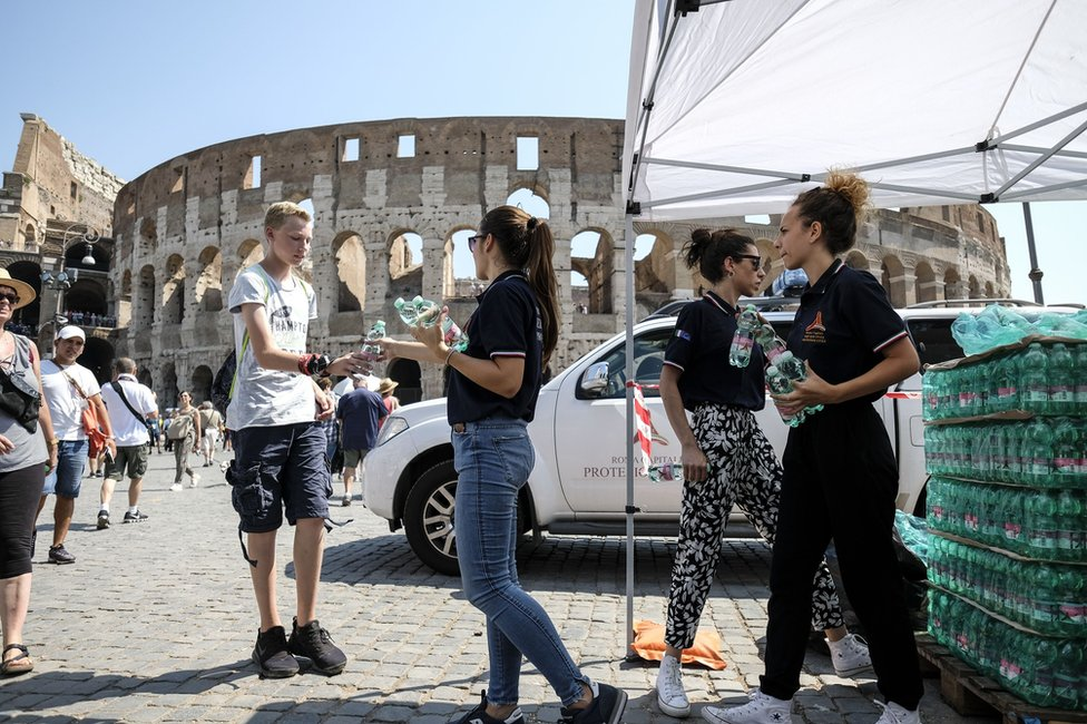 Members of the Italian Civil Protection (Protezione Civile) distribute water bottles to people in front of the Ancient Colosseum, in central Rome