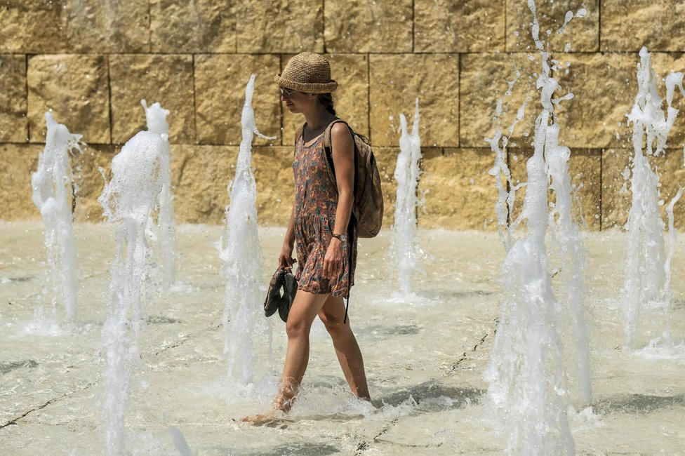A woman cools herself in a fountain near the Ara Pacis monument, in central Rome