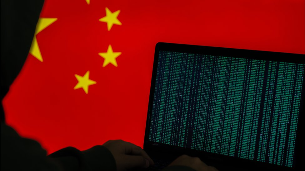 Stock image of hooded person working on computer in front of a Chinese flag