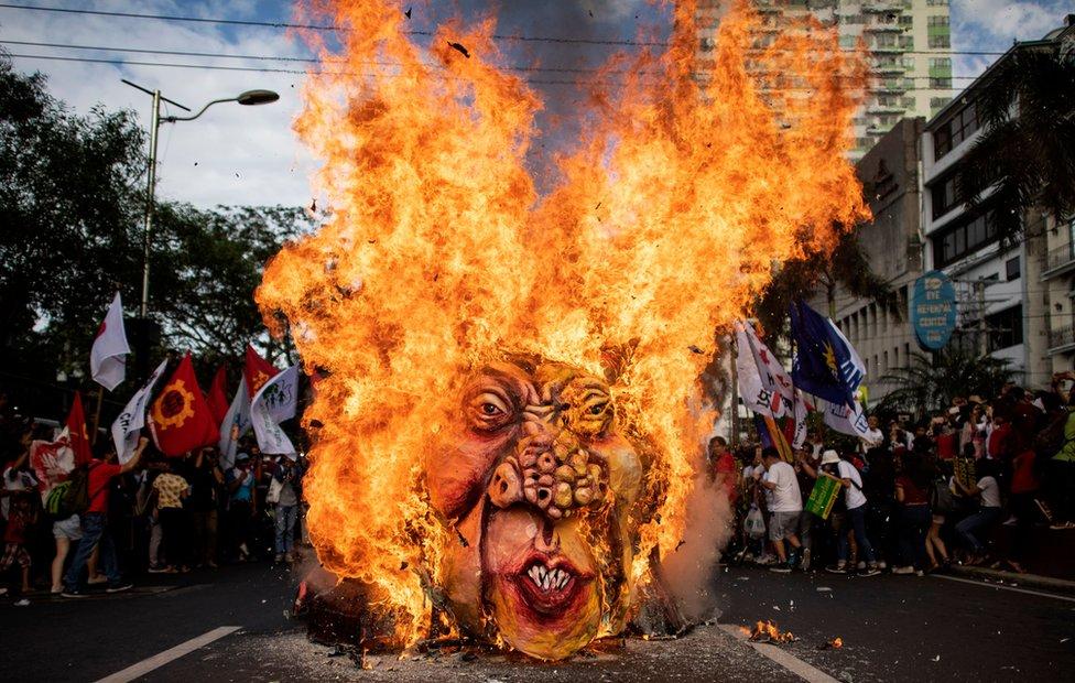 انقلابی رہنما آندرس بونیفاشیو کی 155 ویں سالگرہ کے موقع پر مظاہرین منیلا میں امریکی سفارت خانے کے قریب فلپائن کے صدر رودریگو دترتے کا پتلہ نذر آتش کر رہے ہیں۔