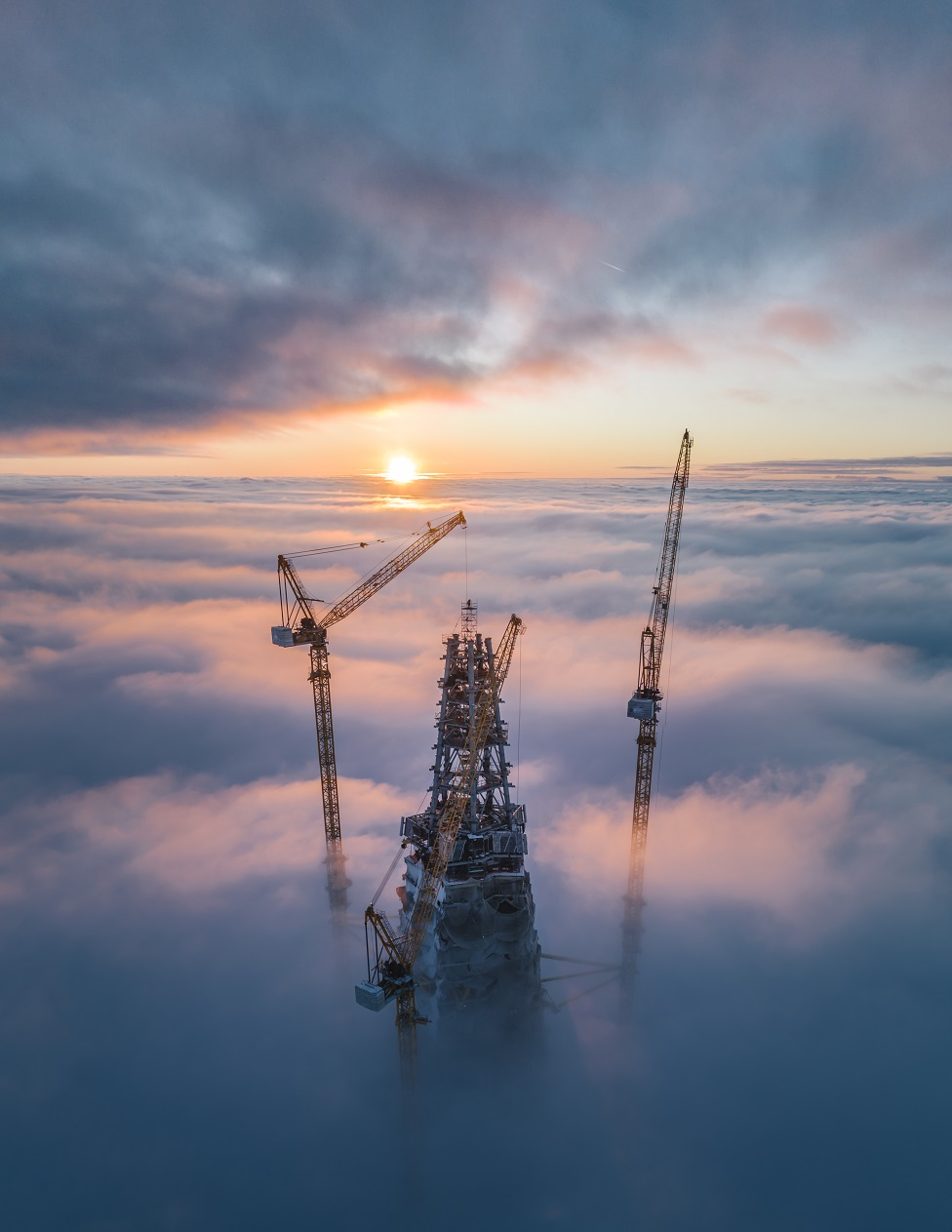 A skyscraper and two cranes poking above clouds