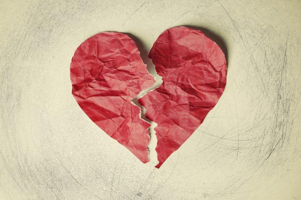 A crumpled paper heart, torn in half
