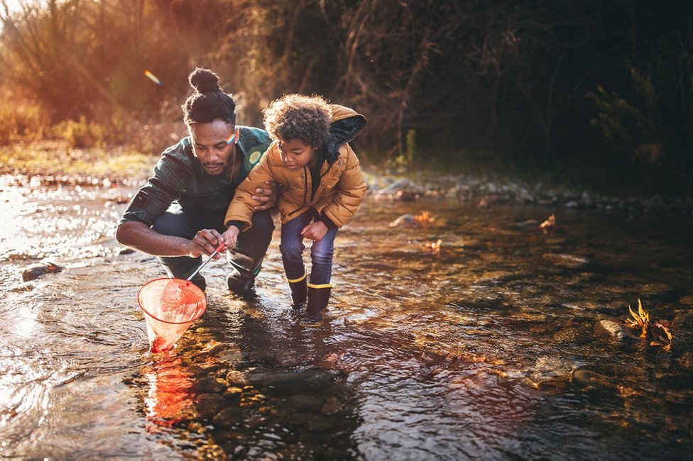 Father and son fishing in a river