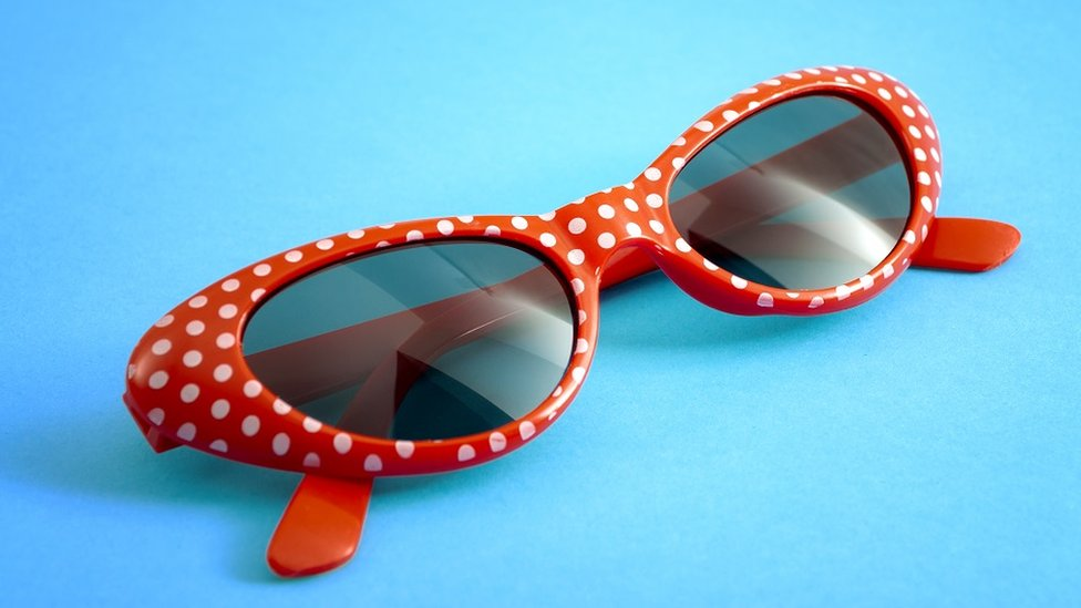Red polka dot sunglasses, on a bright blue background
