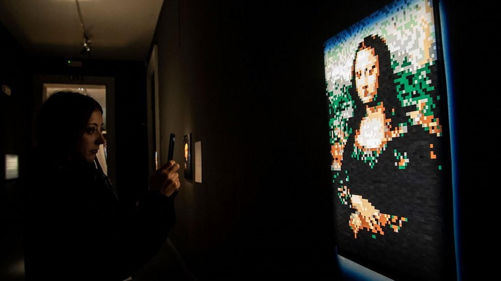 A visitor takes a picture of a sculpture of 'Mona Lisa' made with Lego bricks.