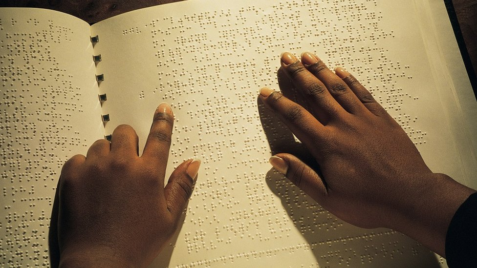 Hands reading Braille book