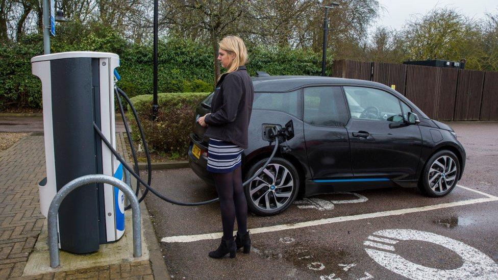 برطانیہ کے علاقے ملٹن کینز میں ایک خاتون اپنی الیکٹرک گاڑی کو چارج کر رہی ہیں