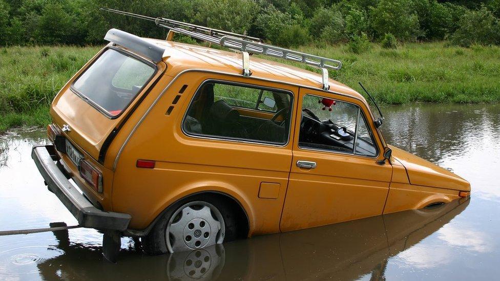 ایک گاڑی پانی میں ڈوب رہی ہے