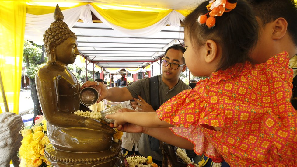 People pour scented water over a statue of a Buddha