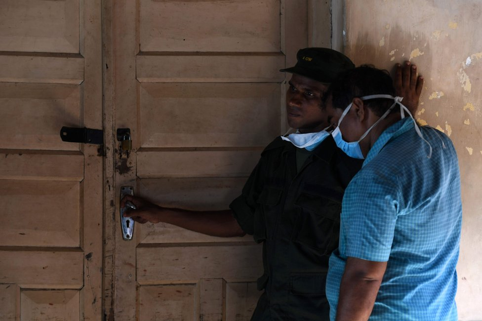 Sri Lankan hospital workers stand at the door to a morgue following a blast in a church in Batticaloa