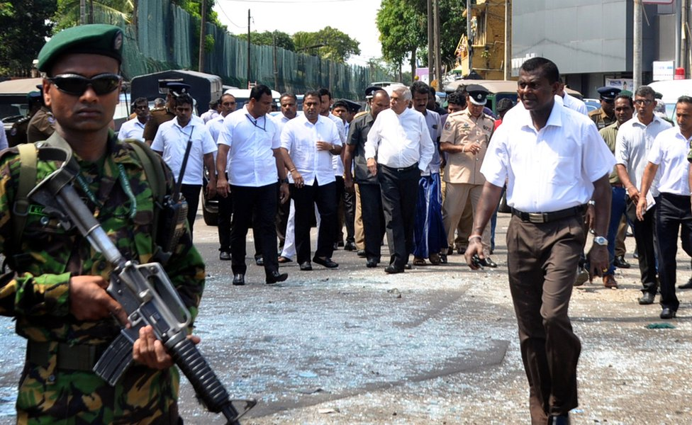 Sri Lankan Prime Minister Ranil Wickremesinghe (C-R) arrives at the scene after an explosion at St Anthony's Church in Kochchikade in Colombo