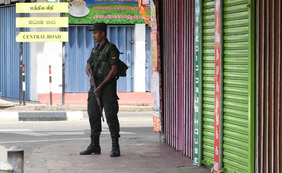 A Sri Lankan soldier stands guard next to closed shops in Batticaloa