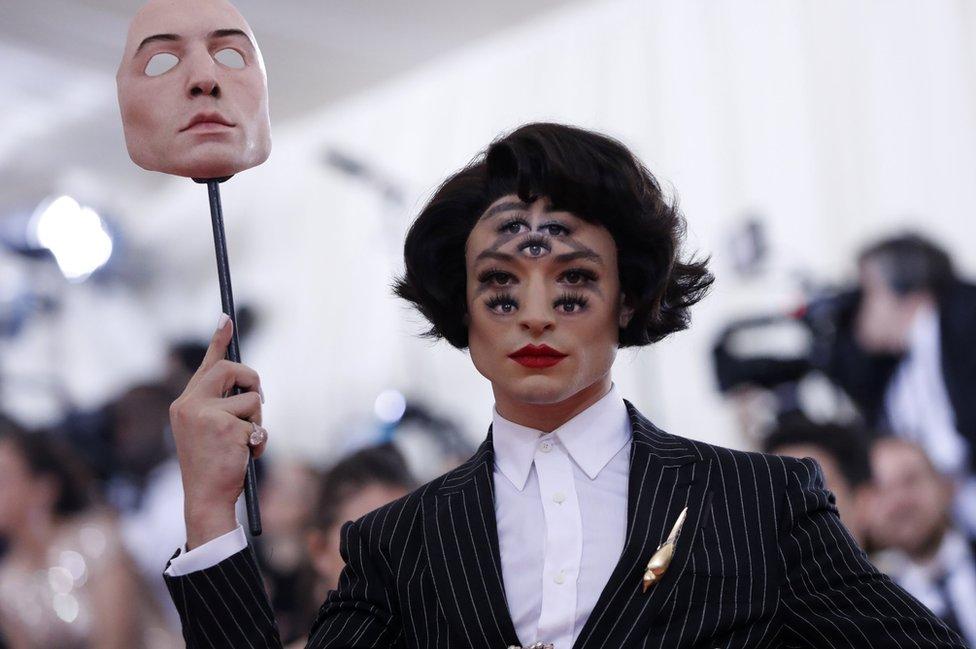 Ezra Miller holds up a mask