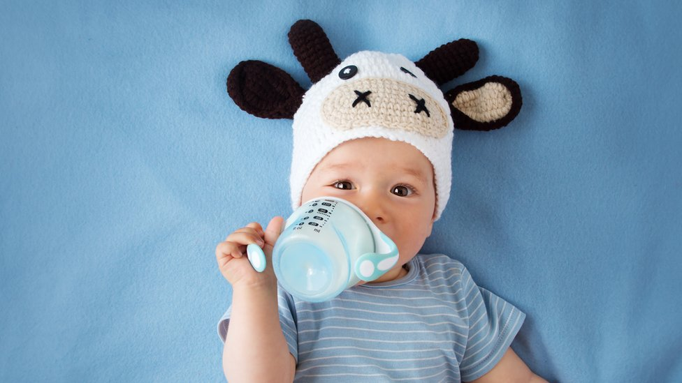 Baby drinking milk from a bottle.