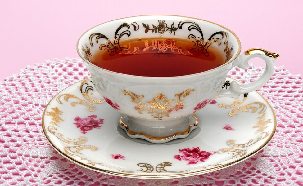 Tea in a fine bone china cup, with gilded decorations and roses painted on