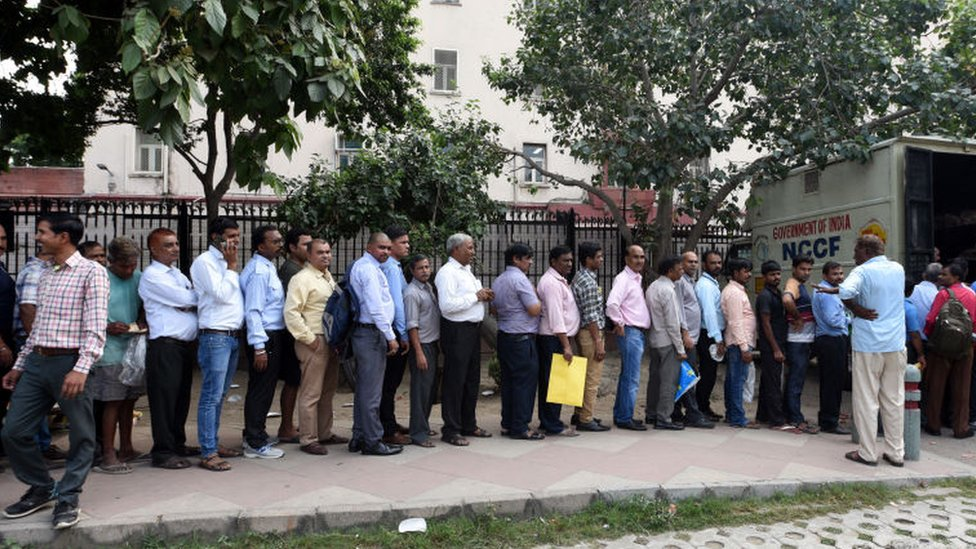 People stand in a queue to buy onions sold at Rs. 22 per kg by the Government of India, outside Krishi Bhawan on September 24, 2019 in New Delhi, India.