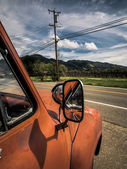 Classic orange old truck with broken side mirror, with road, telephone pole and green hills behind it. Blue sky, midday.