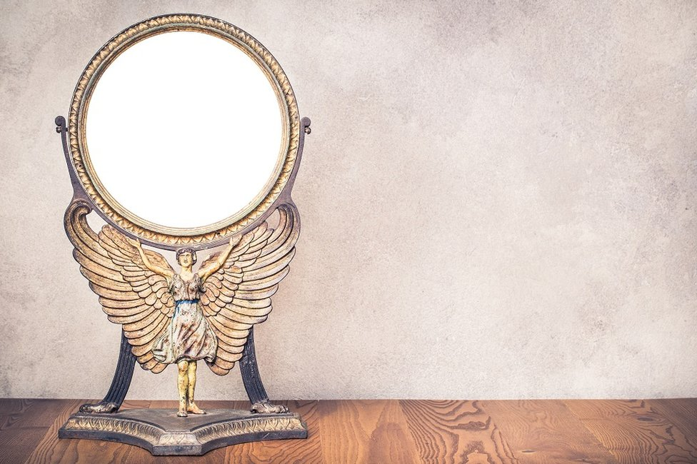 Old antique vintage cast iron desk makeup mirror frame blank holds on the stand in the form of goddess with wings or angel standing on table. Circa end of 1800s or early 1900s.