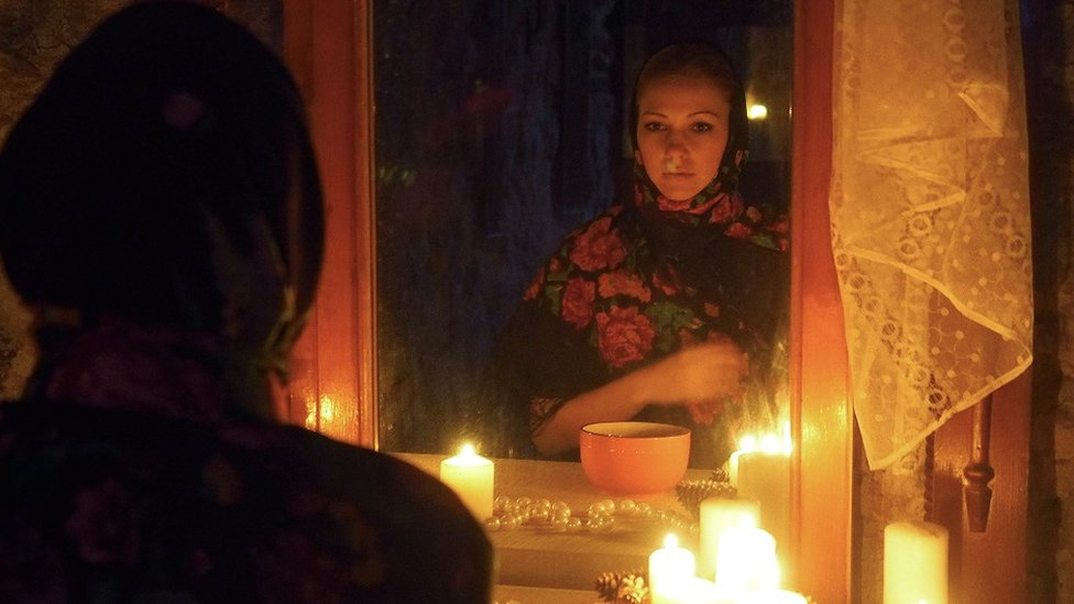 A girl standing in front of a mirror, it's dark and she's using candles for some light.