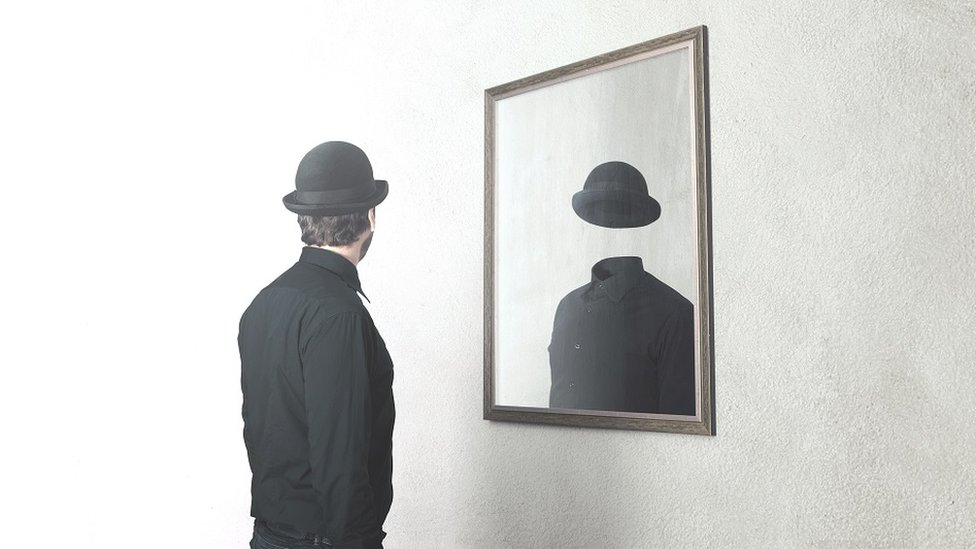 Concept photo, playing on Magritte's surreal painting ideas - man in front of mirror reflecting himself without face