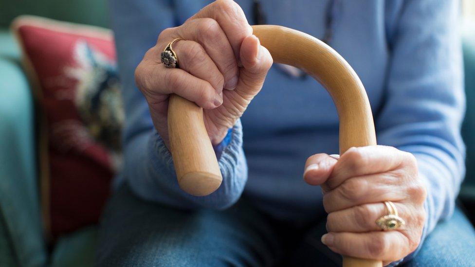 An elderly woman's hand holds a walking stick