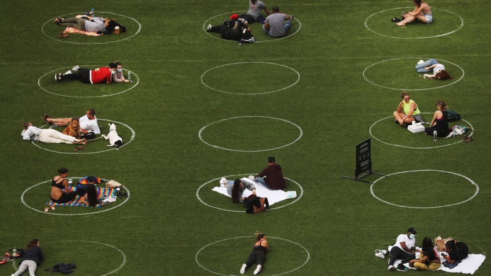 People sit in circles meant to encourage social distancing in Domino Park along the East River on May 18, 2020 in the Williamsburg neighborhood of the Brooklyn borough in New York City
