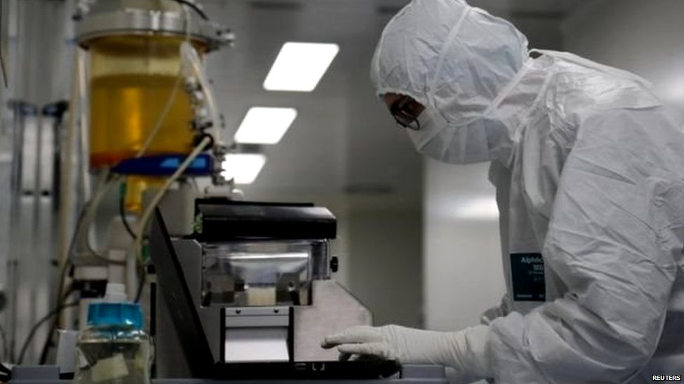 Scientist with full protection gear examining a sample