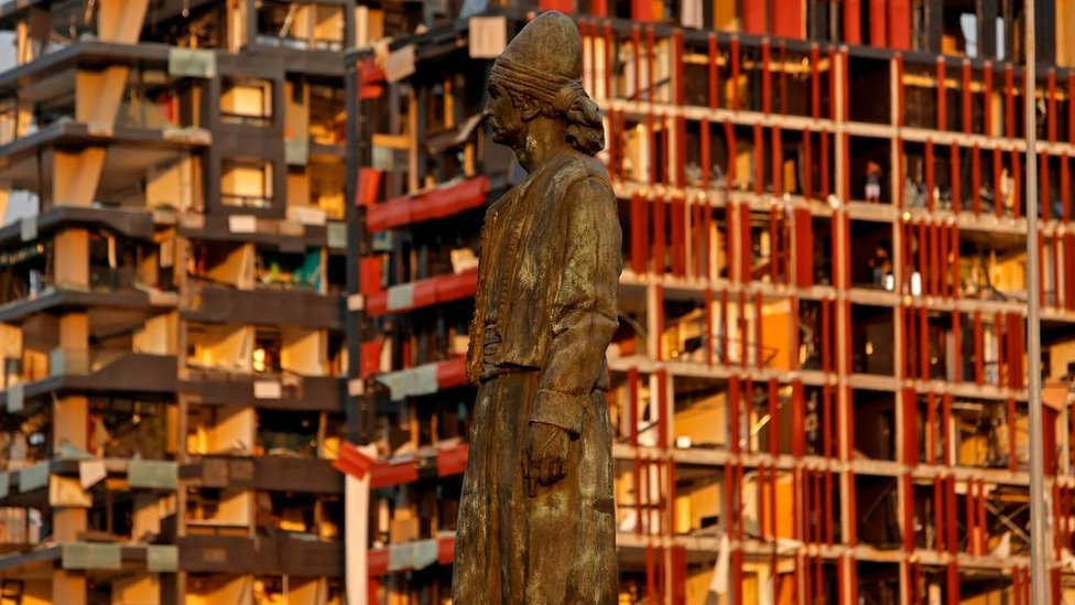 The statue of the Lebanese Emigrant stands intact in front of damaged buildings