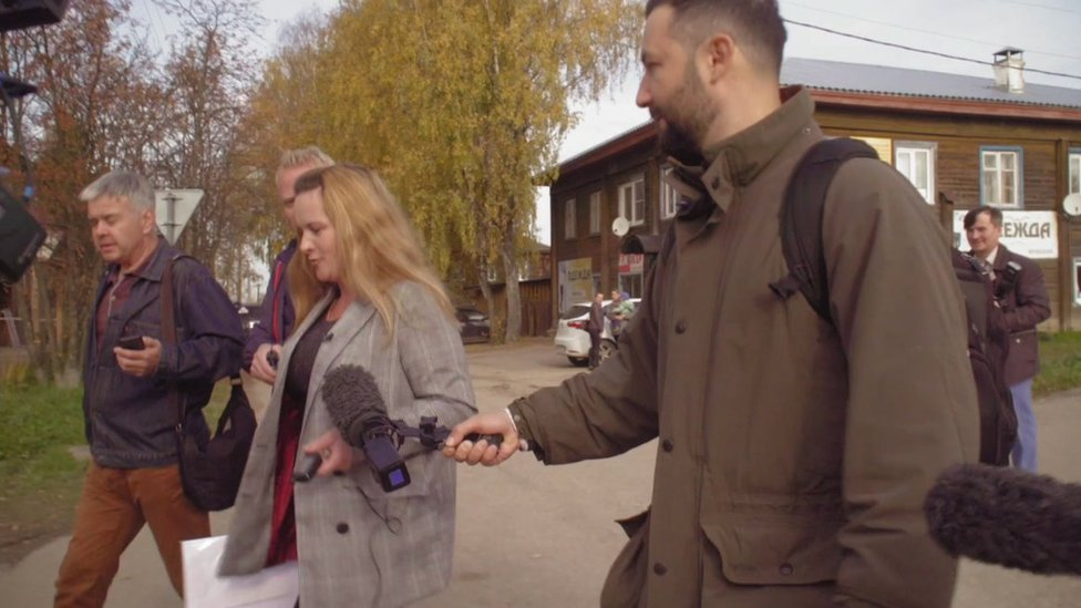 The BBC's Petr Kozlov holds a microphone towards Marina Udgodskaya with other journalists around
