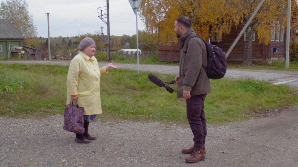 Kozlov holds a microphone towards Udgodskaya's mother-in-law