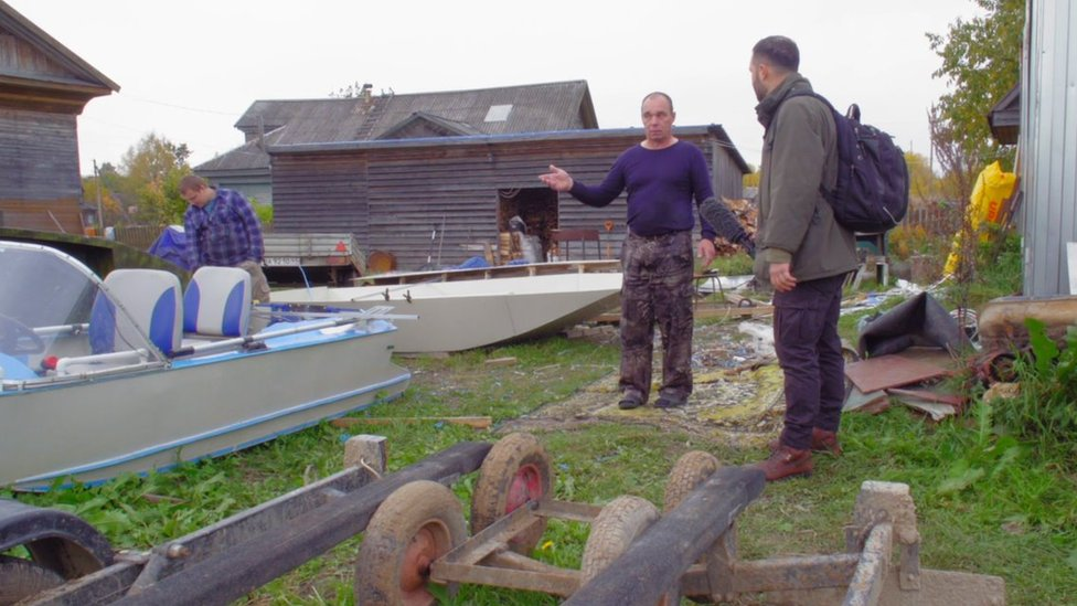 A man talks to a reporter in a boatyard