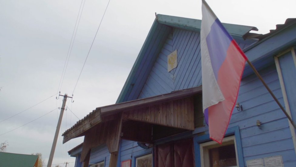 An office building with a Russian flag flying outside