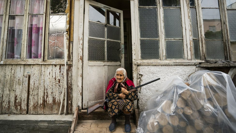 Old woman stands in the entrance of her home with a rifle during the shelling of Stepanakert city