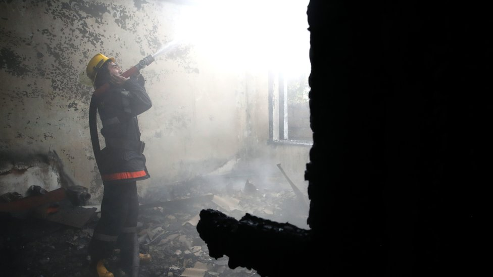 A firefighter battles a fire at a residential building damaged in a shelling attack in Azerbaijan