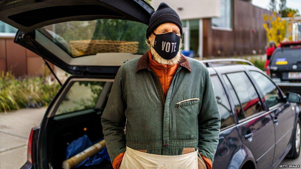 Apple vendor Rikardo Jahnke wears a facemask reading