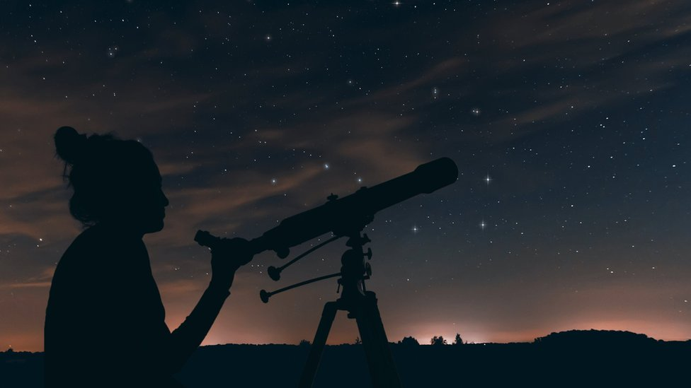 A woman looking at the night sky with a telescope