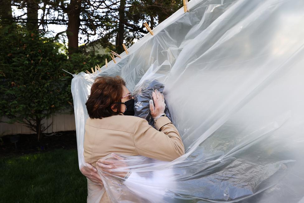24 مئی کو ایک ماں اور بیٹی نیو یارک کے وانتاغ علاقے میں پلاسٹک شیٹ کے اوپر سے ایک دوسرے سے گلے ملتے ہوئے۔