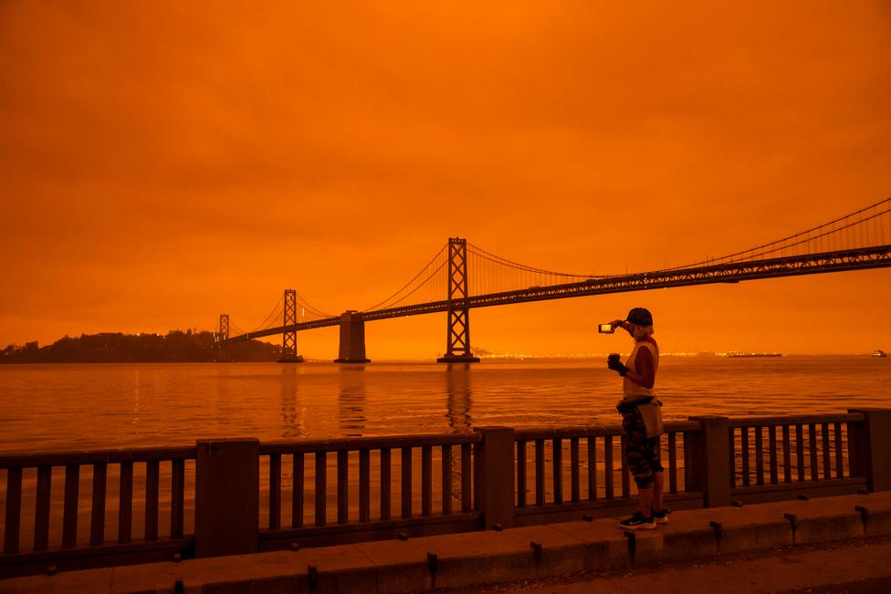 9 ستمبر 2020 کو سان فرانسسکو میں جنگلوں میں لگنے والی آگ کے بعد ایک خاتون اس کی تصویر لیتے ہوئے۔ آسمان مکمل طور پر نارنجی رنگ کا نظر آ رہا ہے۔
