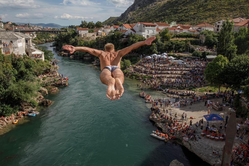 26 جولائی 2020 کو بوسنیا اور ہرزیگوینا کے شہر موستار میں 454 ویں روایتی ڈائیونگ کے مقابلے میں شریک ایک شخص ستاری موسٹ یا پرانے پل سے ڈائیو لگاتے ہوئے۔