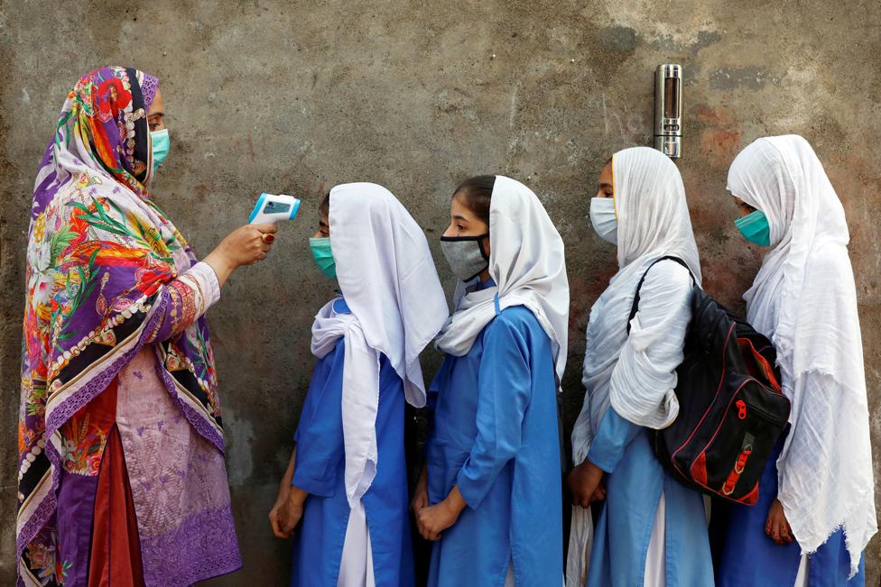 23 ستمبر کو پاکستان کے شہر پشاور کے ایک سکول میں داخل ہونے سے پہلے بچوں کا درجہ حرارت چیک کیا جا رہا ہے۔