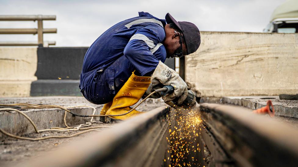 A welder on the Third Mainland Bridge, Lagos, Nigeria
