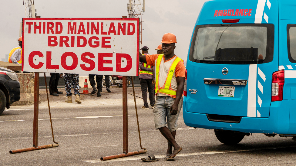 A worker and ambulance on the Third Mainland Bridge, Lagos, Nigeria