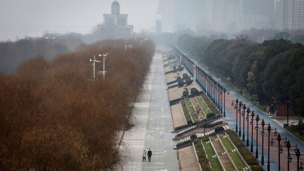 Two people walk down an empty street in Wuhan, 27 January 2020