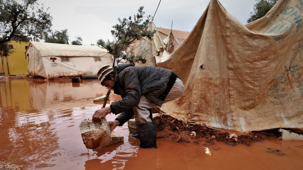 A man stands outside a flooded tent in Idlib province, Syria